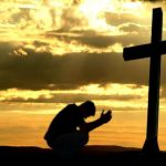 man_praying_before_the_cross